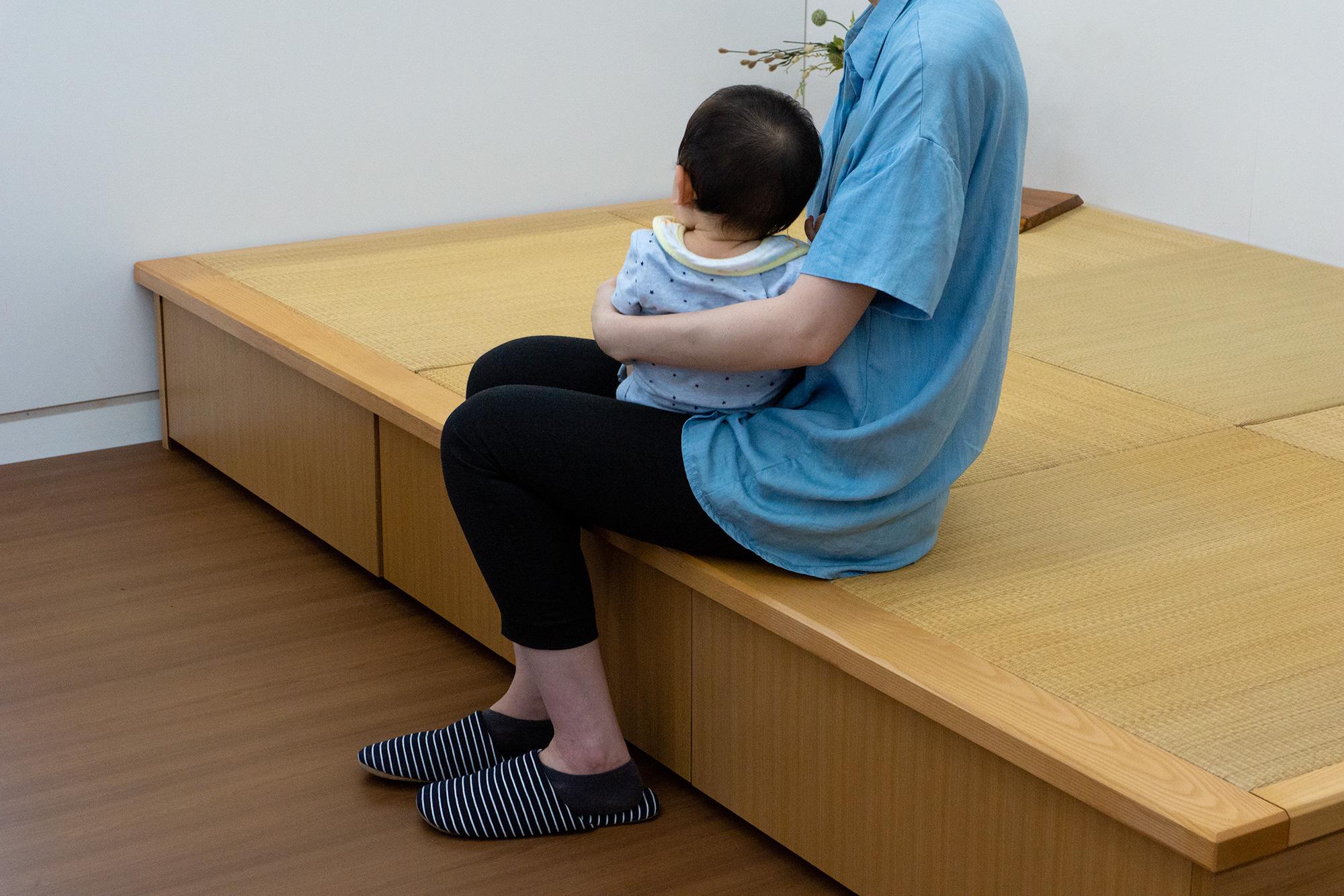 畳ユニットに腰掛けている婦人